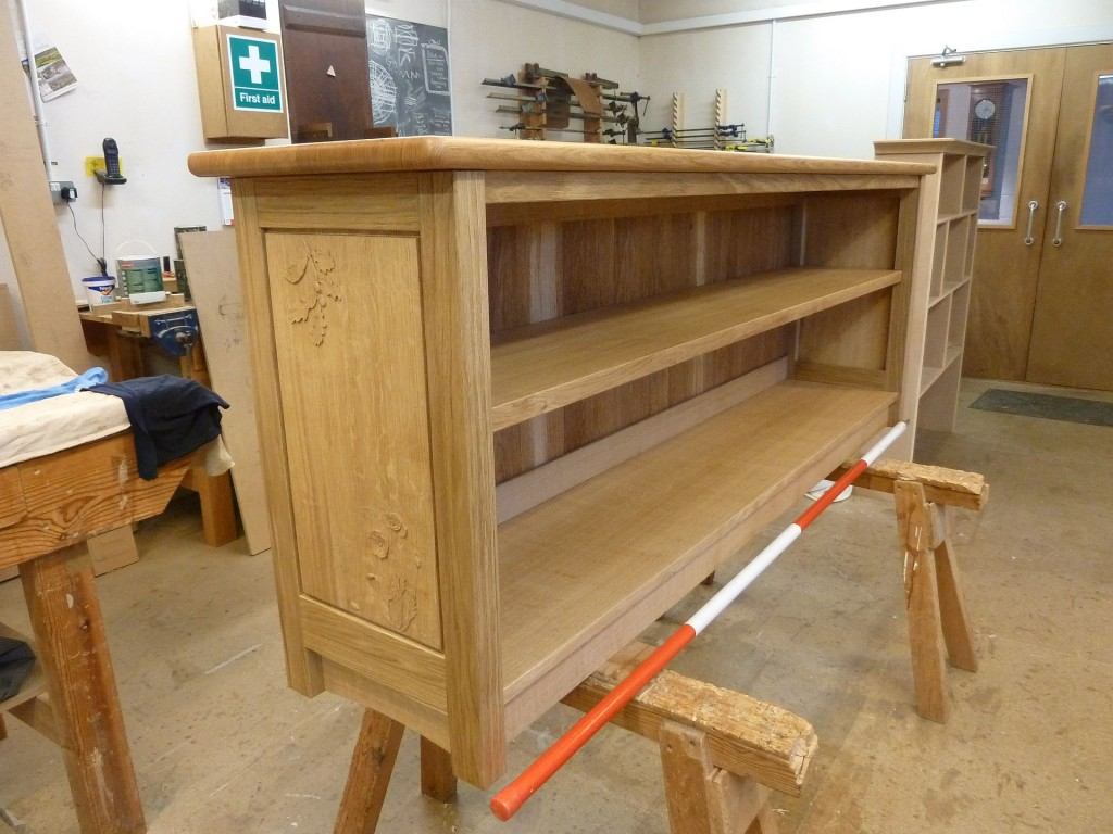 2 metre long bookcase with carved Oak leaves and Poppies.